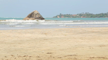 View of sandy beach and small island in Weligama, Sri Lanka.