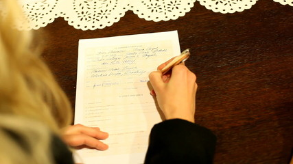 Woman signing wedding document