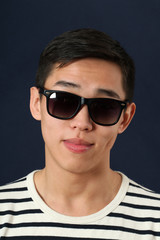 Smiling young Asian man in sunglasses