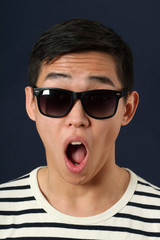 Astonished young Asian man in sunglasses
