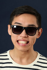 Grinning young Asian man in sunglasses