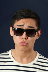 Disappointed young Asian man in sunglasses