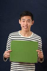 Young Asian man showing green copy space box and looking at came