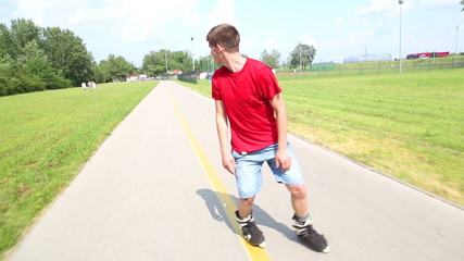 Young handsome man rollerblading in park on a beautiful day, playing around going backwards