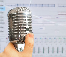 Hand holding retro microphone over recording software.