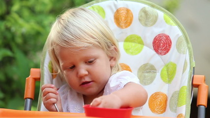little girl sits in chair eats fruit and tries to feed mother