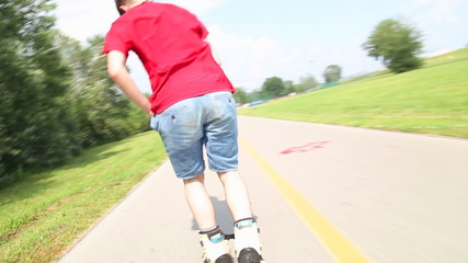 Young handsome man rollerblading in park on a beautiful day, close and doing backwards