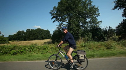 Slow motion - Man cycling on road in countryside