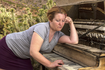 Pensive Woman Playing Antique Piano in Desert