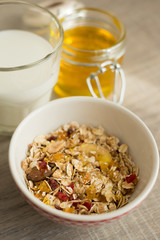 Granola in bowl with honey and milk