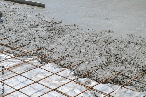 Wet concrete cement flowing over rebar metal - 81250583