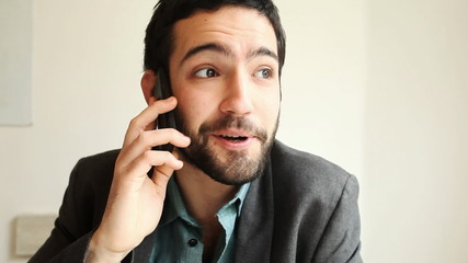 Handsome young man answering a call in a cafe