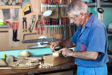 work cabinetmaker marking handcrafted wooden pieces in garage at