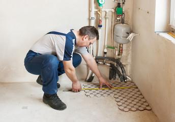 man worker lays on the floor tiles