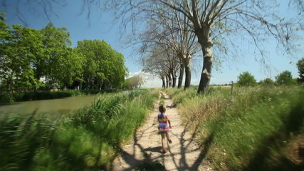 Little girl running along path track in nature