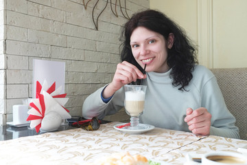Woman with glass of latte sitting in a restaurant