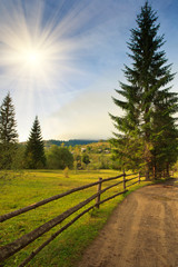 Landscape in a mountain valley: road and wooden fence.