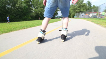 Young handsome man rollerblading in park on a beautiful day, from behind