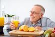 Senior man happy, with a glass of orange juice