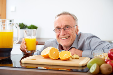 Smiling senior man with a glass of orange juice