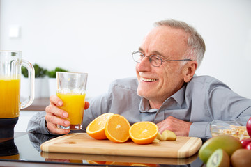 Senior man happy, with a glass of orange juice