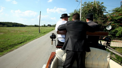 Men sitting on horse drawn carriage on road