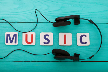 Word music and headphones on blue wooden background