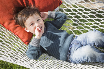 Cute Mixed Race Boy Relaxing in Hammock