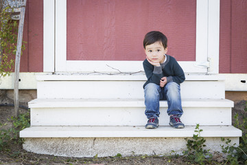 Cute Mixed Race Boy Sitting on the Steps of a Barn