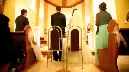 Young couple standing in front of altar at church on wedding day