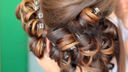 Hair stylist curling hair of future married woman