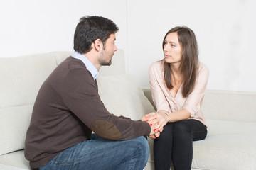 Frau tröstet einen Freund und haelt seine Hand