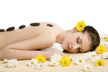 Spa salon: woman relaxing on mat with flowers and stones