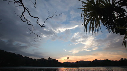 View on the Kandy lake at sunset with reflection of sky in water.