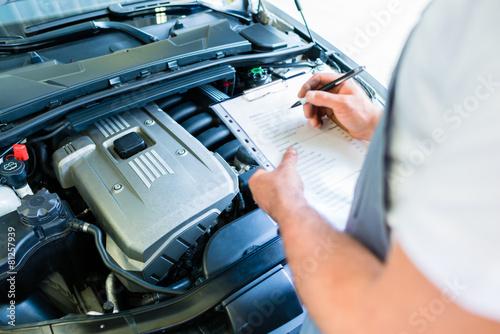 KFZ-Mechaniker mit Checkliste in Autowerkstatt - 81257939
