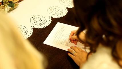 Bride signing matrimonial document