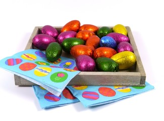 Colorful eggs of chocolate on blue easter napkins