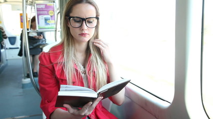 Beautiful young adult woman sitting and reading in tram