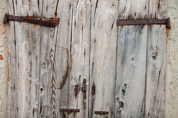 Vecchia porta di doghe di legno con cardini arrugginiti