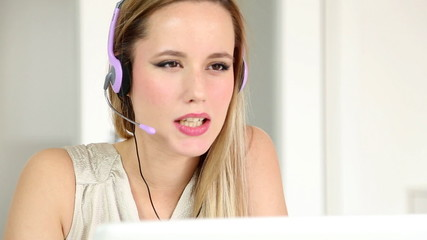 Beautiful young blond telesales woman with headphones on computer talking to customer over the phone