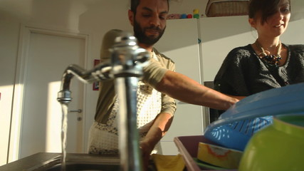 Young couple washing dishes together in the kitchen.