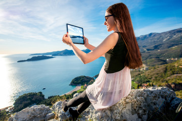 Woman with digital tablet on the mountain top