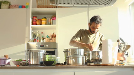 Young Indian man preparing lunch in the kitchen