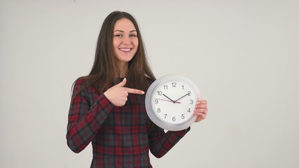 Cute girl pointing at clock on grey background