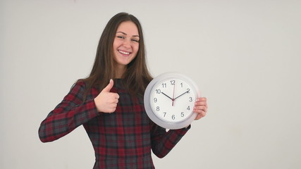 Cute girl pointing at clock and gesturing thumb up sign