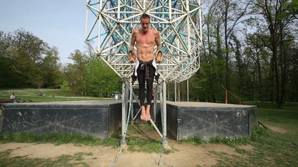 Trained man exercising on gymnastics rings