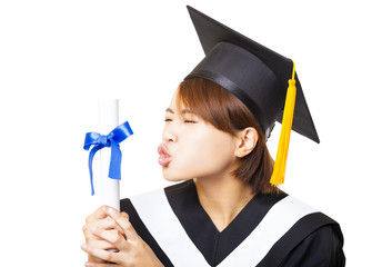 happy young woman graduating kissing diploma
