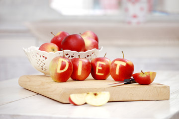 Red apples with the words diet engraved on them and knife