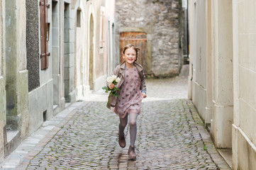 Adorable little girl running in the old town