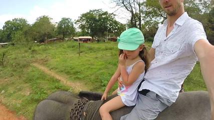 Cute blond girl enjoying elephant ride with her father in Sri Lanka.